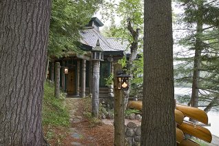 Exterior, horizontal, Lothrup Cabin entry through trees with wooden canoes on rack, Camp Topridge, Paul Smiths, New York, Maple Island Log Homes